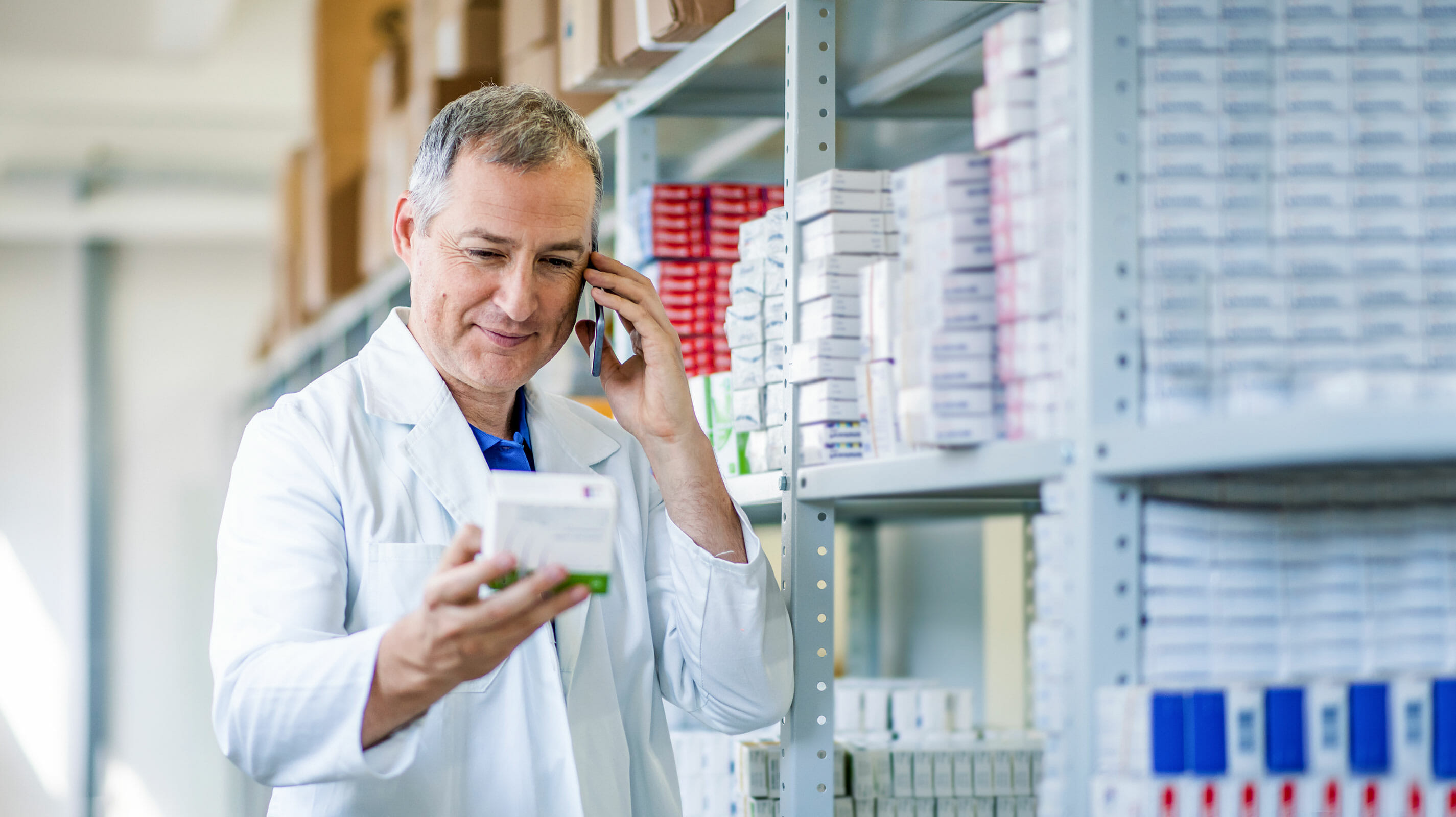 Shot of pharmacist looking at medicine while talking on the phone