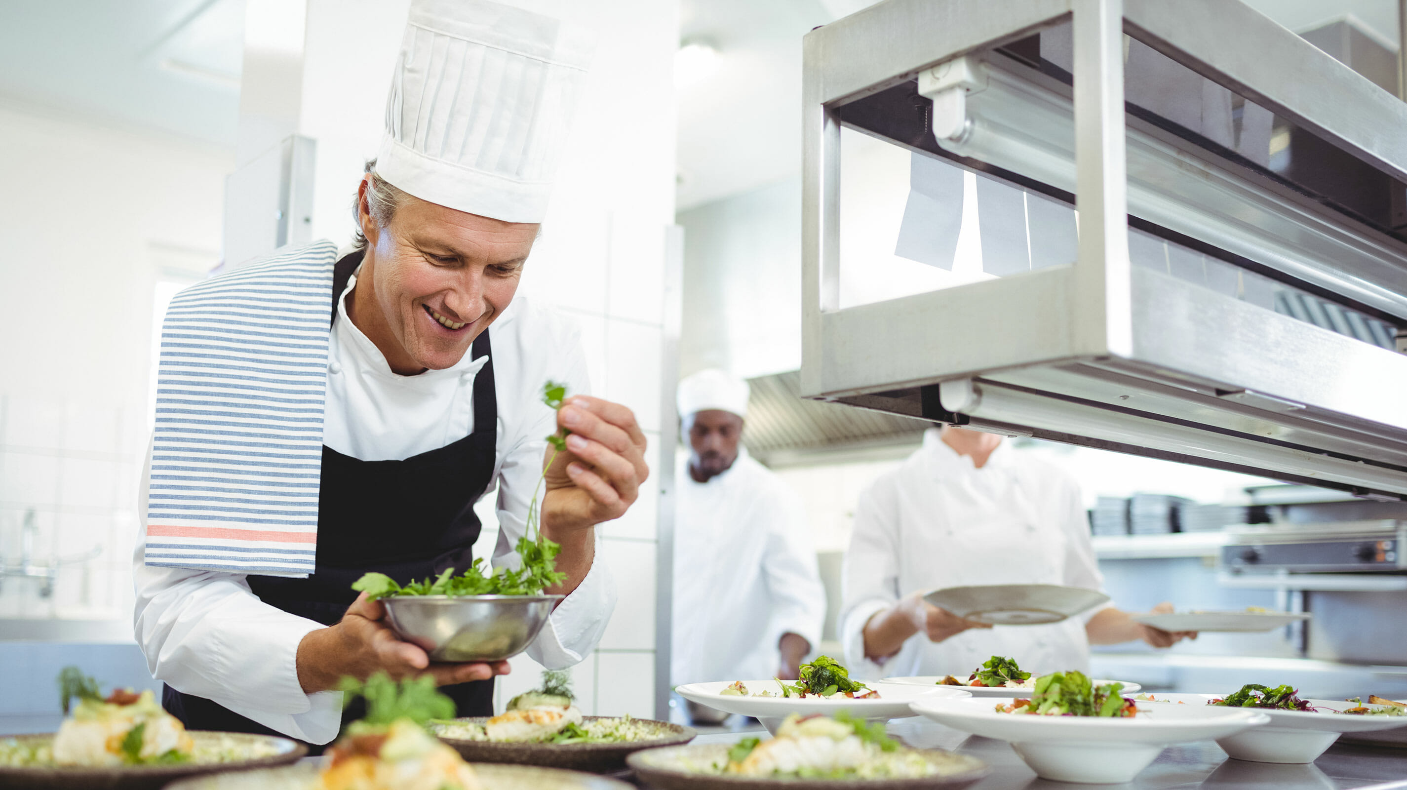 Chef smiling and plating salads